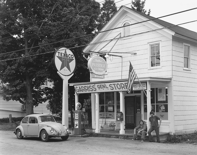 Street photography in black and white by George TICE. The picture represents a car in front of Garriss' General Store